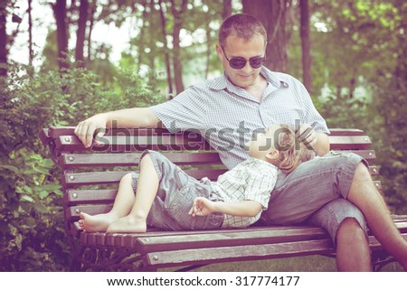 Father and son playing at the park on bench at the day time. Concept of friendly family. - stock photo