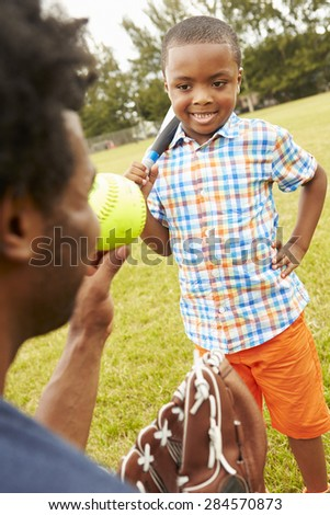 Father And Son Playing Baseball In Park - stock photo