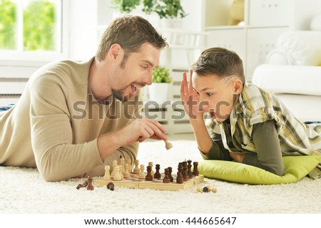 father and son playing chess - stock photo
