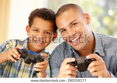 Father and son playing computer games - stock photo