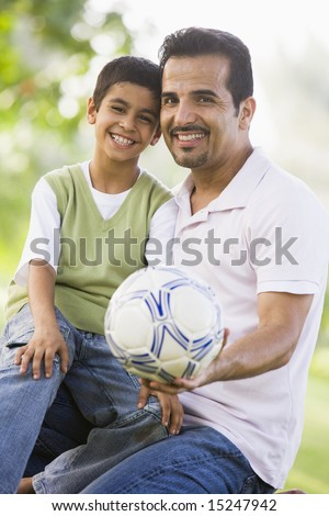 Father and son playing football in park - stock photo