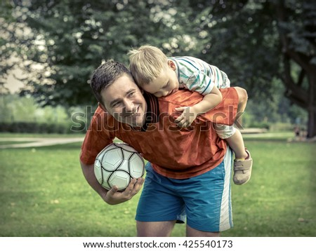 Father and son playing football in park at sunny day - stock photo