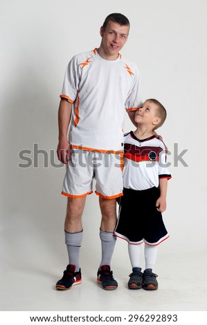 Father and son playing football.Isolated studio portrait - stock photo