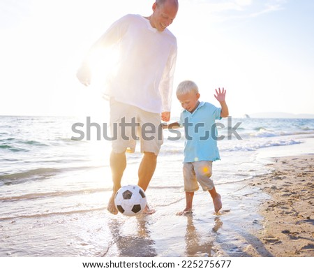 Father and son playing football together. - stock photo