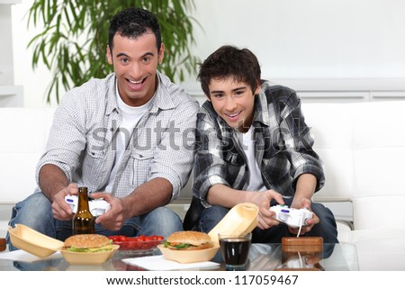 Father and son playing games together - stock photo