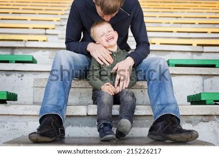 Father and son playing in empty stadium   - stock photo