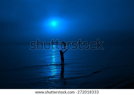 Father and son playing in sunset sea - stock photo