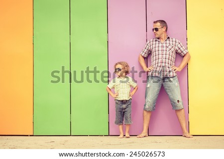 Father and son playing near the house at the day time. They standing near are the colorful wall. Concept of friendly family. - stock photo