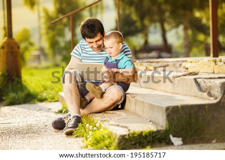 Father and son playing on digital tablet outside - stock photo