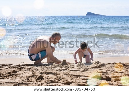 Father and son playing on the beach - stock photo
