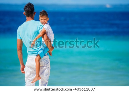 Father and son playing on the beach. - stock photo