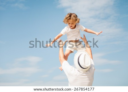 Father and son playing on the beach at the day time. Concept of friendly family. - stock photo
