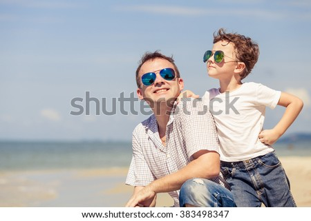 Father and son playing on the beach at the day time. Concept of happy friendly family. - stock photo