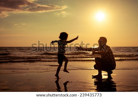 Father and son playing on the beach at the sunset time. - stock photo