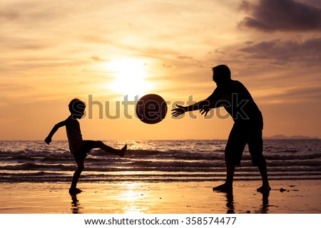 Father and son playing on the beach at the sunset time. Concept of happy friendly family. - stock photo