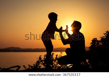 father and son playing on the coast of lake in the mountains of at the sunset time - stock photo