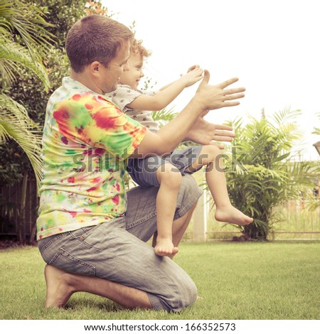 father and son playing on the meadow - stock photo