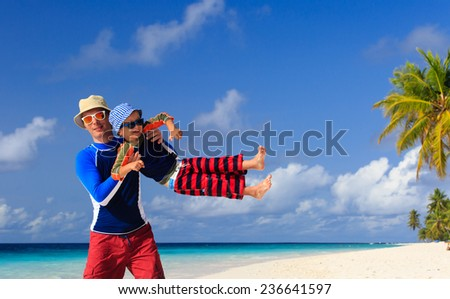 father and son playing on tropical sand beach - stock photo