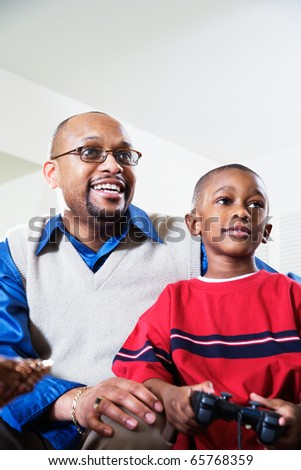 Father and son playing video game - stock photo