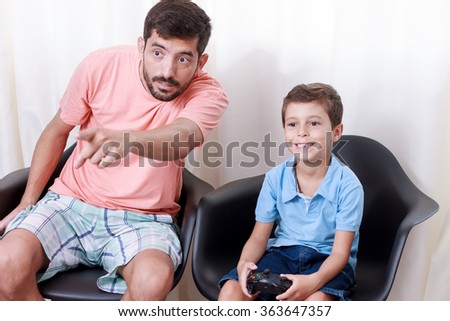 Father and son playing video game in the living room - stock photo