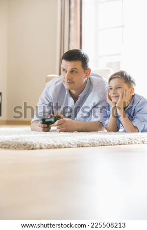 Father and son playing video game on floor at home - stock photo