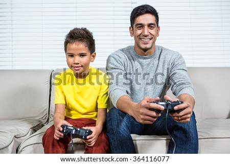 Father and son playing video games on the sofa in living room - stock photo