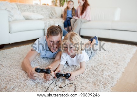 Father and son playing video games together - stock photo