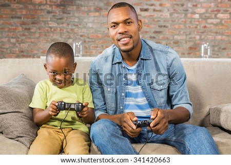 Father and son playing video games together in living room - stock photo
