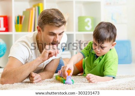 Father And Son Playing With Coloured Blocks At Home - stock photo