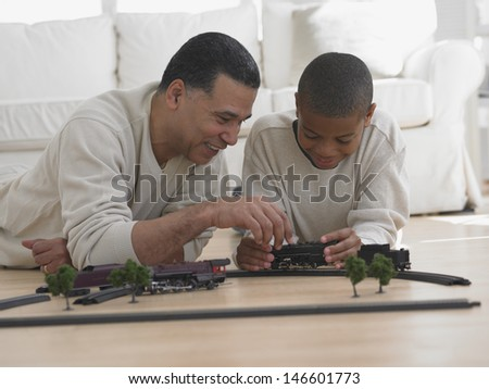 Father and son playing with model train on floor - stock photo