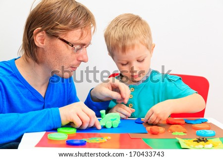 father and son playing with plasticine, early learning and daycare concept - stock photo