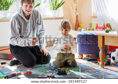 Father and son playing with racing cars on racetrack, indoors, together - stock photo