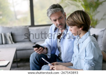 Father and son playing with smartphones - stock photo