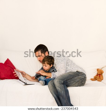 Father and son playing with tablet together on a with sofa - stock photo