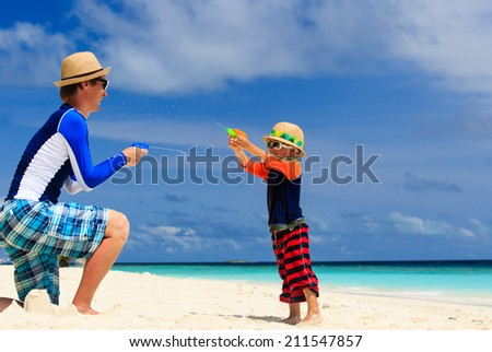 father and son playing with water guns on tropical beach - stock photo