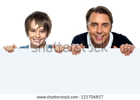Father and son posing behind big blank banner ad. Isolated over white. - stock photo
