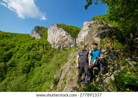 Father and son posing on the high mountains in a sunny spring day - stock photo