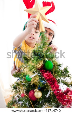 Father and son putting a star on the top of a Christmas tree at home - stock photo