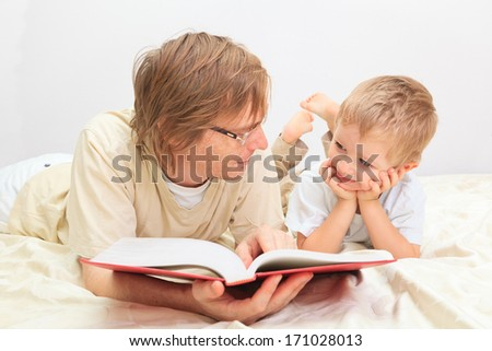 Father and son reading together - stock photo
