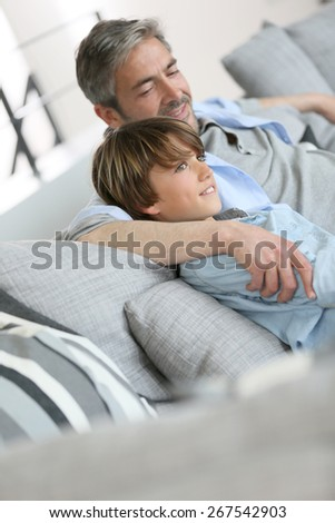 Father and son relaxing in sofa a thome - stock photo