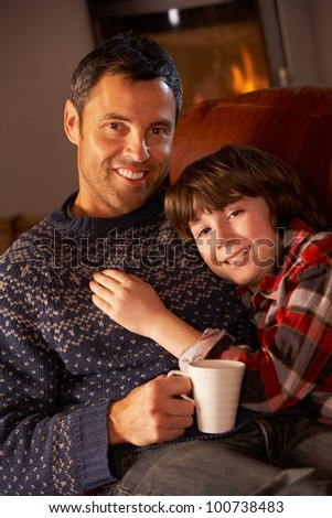 Father And Son Relaxing With Hot Drink Watching TV By Cosy Log Fire - stock photo