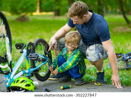 Father and son repairing bike together. - stock photo