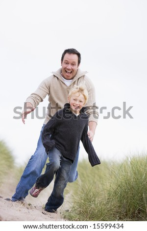Father and son running on beach smiling - stock photo