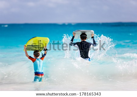 Father and son running towards ocean with boogie boards - stock photo