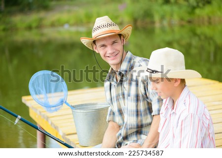 Father and son sitting on bridge and fishing - stock photo