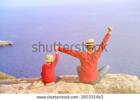 father and son sitting on top of a mountain expressing joy with their arms stretched up towards sky - stock photo