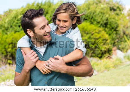 Father and son smiling at each other in the countryside - stock photo