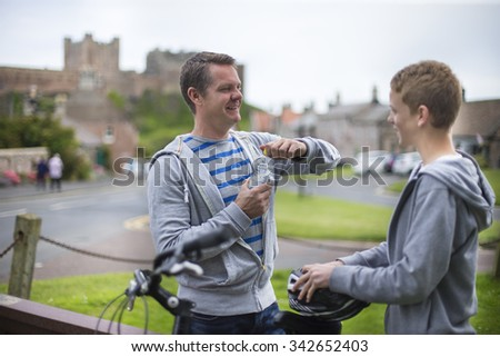 Father and Son stopping in a village in the middle of their bike ride. The father is opening his water while the son holds his helmet.   - stock photo