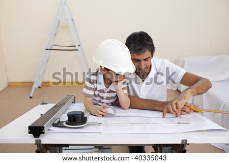 Father and son studying working with plans at home - stock photo