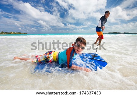 Father and son surfing on boogie boards - stock photo